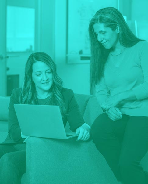 woman showing laptop to another woman